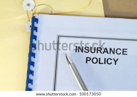 insurance policy folder on desk in office with pen and manila envelop
