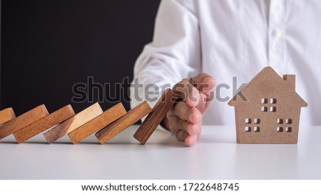 insurance with hands protect a house. Home insurance or house insurance concept