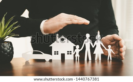Insurer protecting a family, a house and a car with his hands #1440767381