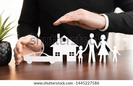 Insurer protecting a family, a house and a car with his hands #1445227586