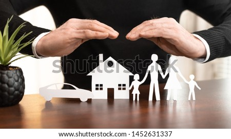 Insurer protecting a family, a house and a car with his hands #1452631337