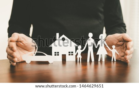 Insurer protecting a family, a house and a car with his hands #1464629651