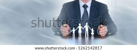 Insurer protecting a family with his hands. panoramic banner #1262142817