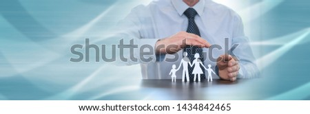 Insurer protecting a family with his hands; panoramic banner #1434842465