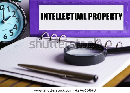 Intelectual Property - Purple Office Folder on Background of Working Table with Magnifying glass,  a pen and clock - business and finance concept