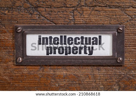 intellectual property  - file cabinet label, bronze holder against grunge and scratched wood