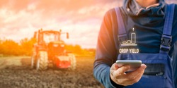 Intelligent agriculture concept with crop yield. Farmer or agrarian with smart phone looking on growing efficiency and crop yield, tractor in background. Smart agriculture and automation concept.