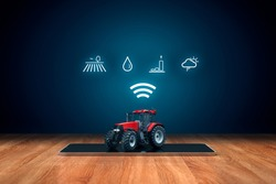 Intelligent agriculture concept with digital tablet, tractor and icons symbolizing data about fields, soil moisture, crop yield (productivity and efficiency) and weather forecast.