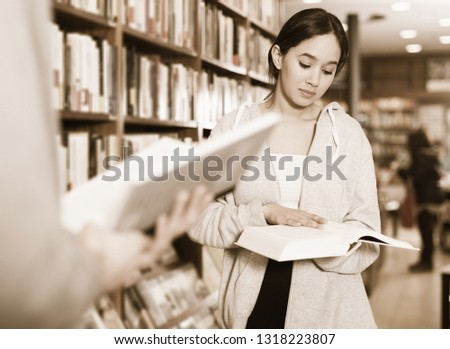 Intelligent Brazilian girl browsing textbooks in bookstore #1318223807