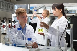 Intelligent Chinese female working with reagent in test tube during chemical experiment with male fellow student in university lab. Focus on male
