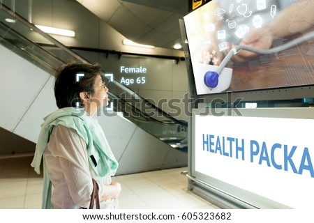 Intelligent Digital Signage marketing and face recognition concept. Old woman watch interactive artificial intelligence digital advertisement about healthcare package in retail shopping Mall.