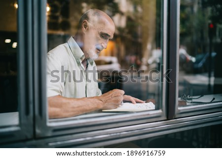 Intelligent elderly male teacher in casual clothing analyzing reminder schedule noted in education textbook, aged Caucasian man checking information from noted spending daytime for planning Foto d'archivio ©