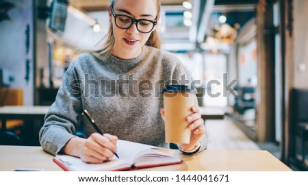 Intelligent female student in spectacles notes information to textbook while spending time in cafeteria for drinking caffeine beverage, clever hipster girl in casual wear doing school homework