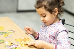 intelligent girl wearing white shirt gathers difficult puzzle consisting of small pieces on wooden table close view