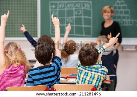 Intelligent group of young school children all raising their hands in the air to answer a question posed by the female teacher, view from behind