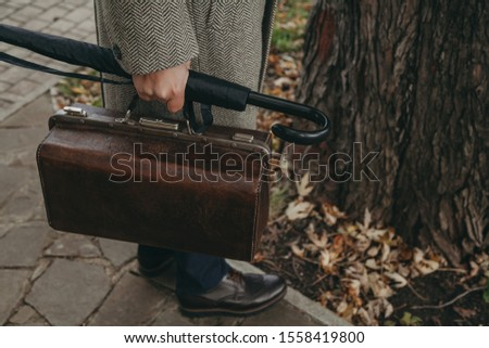Intelligent in the autumn park. A man in a gray coat is standing in the autumn park. In the hand an umbrella-cane and a valise