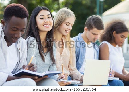 Intelligent international students preparing for final exams at public park, using laptop and notebooks ストックフォト ©