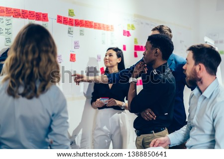 Intelligent male and female managers pondering on ideas for business plan for company, creative group of diversity people in formal wear thinking together about startup project making notes on stick #1388850641
