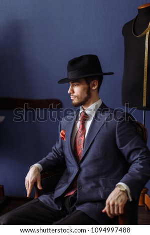 Intelligent Man in tailored classy jacket and classy hat posing indoors at dressmakers salon #1094997488