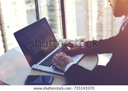 Intelligent man managing director is keyboarding on laptop computer, while is sitting in modern office interior. Successful male economist is analyzing the activities of the company via net-book