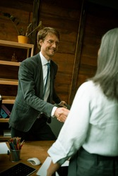 Intelligent man shakes the hand of a gray hair woman standing with back in foreground. Focus on young smiling businessman. Handshake concept. Dutch angle shot.