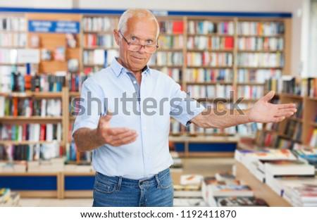 Intelligent mature man politely inviting to modern bookstore