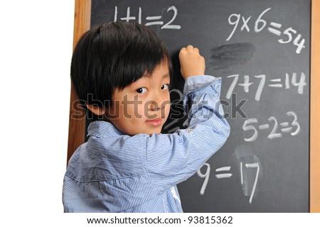 Intelligent schoolboy writing on blackboard ( good at figures )