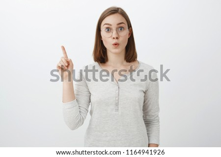 Intelligent smart and creative female coworker in trendy glasses and blouse raising index finger in eureka gesture folding lips, staring excited at camera being striked with plan over gray background