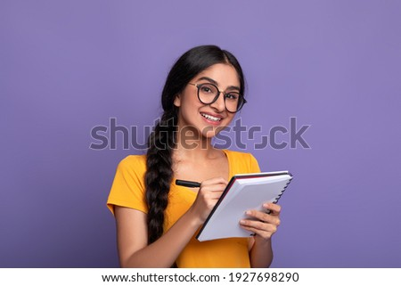 Intelligent young asian woman in glasses smiling and taking notes, holding notepad and pen, isolated over purple studio background, copy space. Cheerful smart lady planning her day, writing tasks Stock photo ©