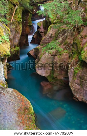 Intense blue glacial melt water rushing through the narrow canyon of Avalanche Gorge, Glacier National Park.