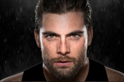 Intense eyes stare powerful expression determined focused conviction from masculine athlete rain