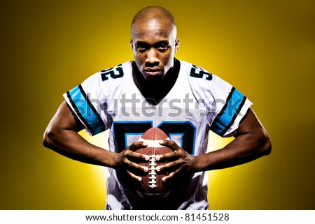 Intense football player holding a ball against a golden background