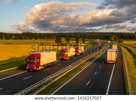 intensive highway traffic at sunset - column of trucks on the motorway in Poland #1432217027