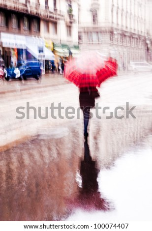 Intentionally motion blurred abstract image of a woman walking with a red umbrella under the rain. Shot in Milan, Italy