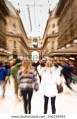 Intentionally motion blurred creative image of people walking in Galleria Vittorio Emanuele II in Milan, Italy. The gallery is one of the most famous landmarks in Milan and a famous shopping street.