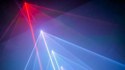 Interactive exposition in modern science museum or exhibition: bright laser show installation with color rays or beams in dark room. Performance, technology, visuals, digital, contemporary art concept