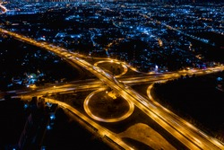 interchange freeway high way motorway and ring road transportation logistics connect in the city with lighting the city background at night in Thailand aerial view