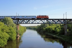 Intercity train passing the steel bridge over the river