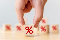 Interest rate financial and mortgage rates concept. Hand choosen wooden cube block with icon percentage symbol