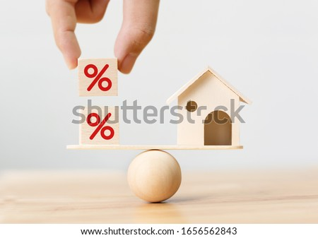 Interest rate financial and mortgage rates concept. Wooden home and hand putting cube block shape with icon percent on wood scales Foto stock ©