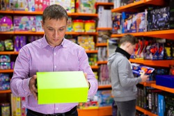 Interested adult man shopping in store of kids toys, holding carton with new plaything