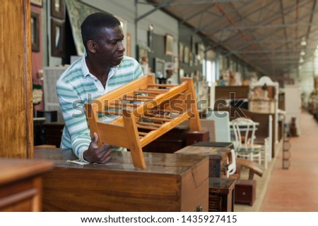 Interested African-American man choosing  furniture for apartment in furnishing salon  #1435927415