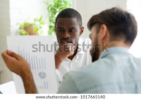 Interested black client listens to financial advisor explaining new project investment, african and caucasian businessmen discuss statistics data report, excited by business growth or profit increase