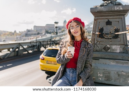 Interested brown-haired woman in blue denim pants holding cup of cappuccino on sky background in cold day. Photo of enchanting confident girl drinking coffee on the road.