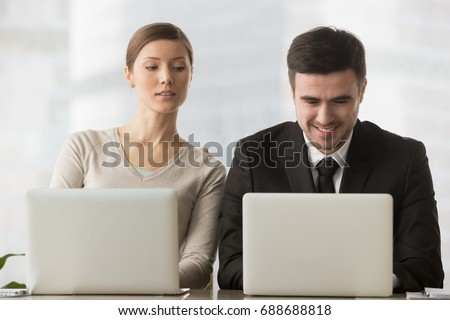 Interested curious corporate spy looking at colleagues laptop, spying on rival, cheating on examination, stealing idea, sneaking peek, taking inquisitive glance at computer screen of unaware coworker - Shutterstock ID 688688818