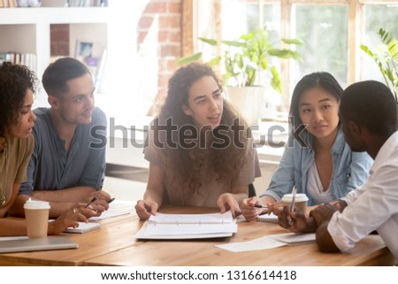 Interested diverse colleagues listening to african coworker telling new idea at group meeting, black team member speak share opinion with multi ethnic employees during corporate brainstorm discussion