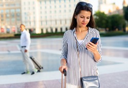 Interested female traveler walking with luggage along foreign city streets, reading about sights in smartphone..