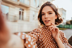 Interested glamorous woman in brown attire making selfie. Magnificent brunette girl taking picture of herself while walking around town.