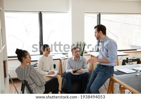 Interested happy young multiracial colleagues sitting on chairs, listening to male boss team leader, explaining working issues at briefing meeting in modern office, international company collaboration
