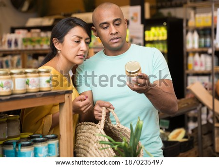 Interested Latin American couple reading product label on jar while choosing groceries in supermarket